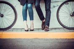 Pares novos que sentam-se em uma bicicleta oposto à cidade fotografia de stock