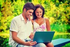 Pares novos que sentam-se guardando o portátil que olha nele e que sorri dentro Fotografia de Stock Royalty Free