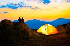 Pares novos que sentam-se na rocha perto da barraca iluminada e que olham a noite bonita Mountain View com céu do por do sol fotos de stock royalty free
