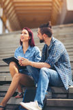 Pares novos que sentam-se nas escadas em escadas do campus universitário Imagens de Stock