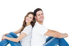 Pares novos que sentam-se no assoalho de volta à parte traseira Fotografia de Stock Royalty Free