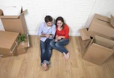 Pares novos que sentam-se no assoalho que move-se na casa nova usando a almofada digital da tabuleta fotografia de stock royalty free