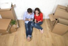 Pares novos que sentam-se no assoalho que move-se na utilização da casa nova digital fotografia de stock royalty free