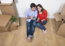 Pares novos que sentam-se no assoalho que move-se na utilização da casa nova digital foto de stock royalty free