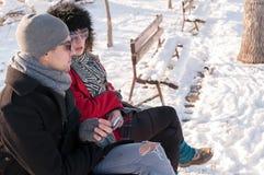 Pares novos que sentam-se no banco no inverno Fotografia de Stock Royalty Free