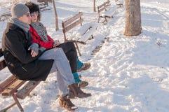 Pares novos que sentam-se no banco no inverno Fotos de Stock Royalty Free