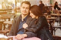 Pares novos que sentam-se no caf? da rua no alargamento do sol T?mara rom?ntica imagem de stock royalty free