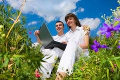 Pares novos que sentam-se no campo de grama com portátil Imagens de Stock Royalty Free
