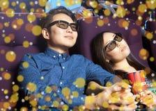 Pares novos que sentam-se no cinema que veste os vidros 3d, olhando Fotografia de Stock