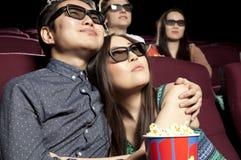 Pares novos que sentam-se no cinema que veste os vidros 3d, olhando Fotografia de Stock Royalty Free