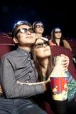 Pares novos que sentam-se no cinema que veste os vidros 3d, olhando Imagens de Stock
