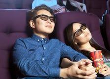 Pares novos que sentam-se no cinema que veste os vidros 3d, olhando Foto de Stock