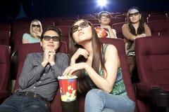 Pares novos que sentam-se no cinema que veste os vidros 3d, olhando Imagem de Stock