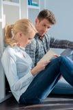 Pares novos que sentam-se no livro de leitura do assoalho Foto de Stock Royalty Free