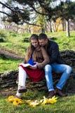 Pares novos que sentam-se no parque e na leitura foto de stock royalty free