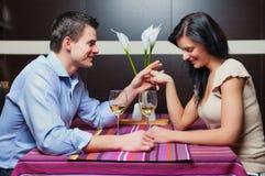 Pares novos que sentam-se no restaurante e que flertam Imagens de Stock Royalty Free