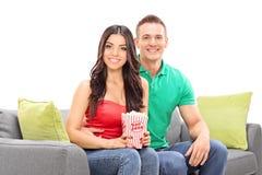 Pares novos que sentam-se no sofá com a caixa da pipoca Fotografia de Stock