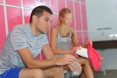 Pares novos que sentam-se no vestuário dos gyms imagens de stock