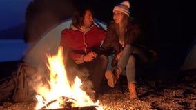 Pares novos que sentam-se pelo fogo Acampamento com as barracas pelo mar Noite da mola vídeos de arquivo