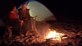 Pares novos que sentam-se pelo fogo Acampamento com as barracas pelo mar Noite da mola video estoque