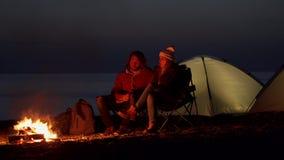 Pares novos que sentam-se pelo fogo Acampamento com as barracas pelo mar sequência do vídeo três filme