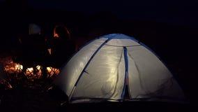 Pares novos que sentam-se pelo fogo Acampamento com as barracas pelo mar vista traseira por handheld video estoque