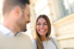 Pares novos que sorriem ao andar fora em d ensolarado fotos de stock