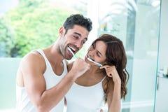Pares novos que sorriem ao escovar os dentes foto de stock