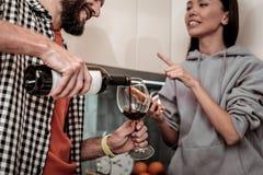 Pares novos que têm a conversação ao beber o vinho em casa imagem de stock