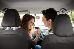 Pares novos que têm o divertimento dentro de um carro Fotos de Stock Royalty Free