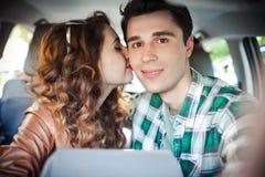 Pares novos que têm o divertimento dentro de um carro e que fazem o selfie Foto de Stock Royalty Free