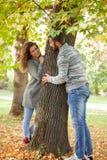 Pares novos que têm o divertimento em madeiras outonais, pares que espreitam de b Fotografia de Stock