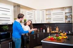 Pares novos que têm o divertimento na cozinha Fotografia de Stock
