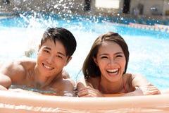 Pares novos que têm o divertimento na piscina Fotografia de Stock