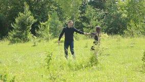 Pares novos que têm o divertimento no campo verde na primavera ou no verão, plano geral filme