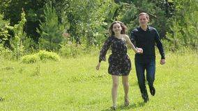 Pares novos que têm o divertimento no campo verde na primavera ou no verão, plano geral video estoque