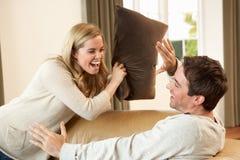 Pares novos que têm o divertimento no sofá Fotos de Stock