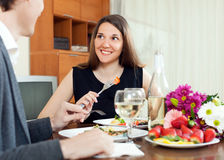 Pares novos que têm o jantar romântico com champanhe Fotos de Stock