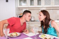 Pares novos que têm o jantar romântico em casa foto de stock