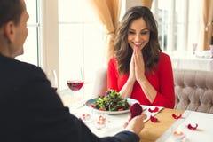 Pares novos que têm o jantar romântico na caixa do anel da proposta do restaurante foto de stock royalty free