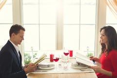Pares novos que têm o jantar romântico no menu da visão do restaurante fotografia de stock royalty free
