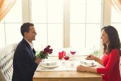 Pares novos que têm o jantar romântico no ramalhete das rosas do restaurante imagem de stock
