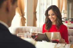Pares novos que têm o jantar romântico no restaurante que guarda a escolha do menu imagens de stock royalty free