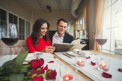 Pares novos que têm o jantar romântico no restaurante que guarda a escolha do menu fotos de stock royalty free