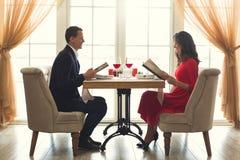 Pares novos que têm o jantar romântico no restaurante que guarda o menu foto de stock