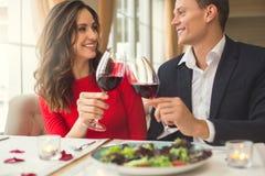 Pares novos que têm o jantar romântico no restaurante que senta-se unida mantendo a opinião dianteira de vidros de vinho imagem de stock