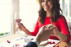 Pares novos que têm o jantar romântico no restaurante que veste um sorriso do anel da proposta fotos de stock royalty free