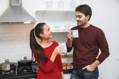 Pares novos que têm o nivelamento romântico em casa na cozinha que bebe o café quente imagem de stock royalty free