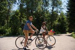 Pares novos que têm o passeio alegre da bicicleta na natureza Fotografia de Stock