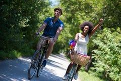Pares novos que têm o passeio alegre da bicicleta na natureza Foto de Stock Royalty Free